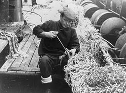 Black and white photograph of man mending a fishing net